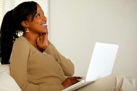 Portrait of a lovely young woman working on laptop while looking up and smiling Stock Photo - 14795020