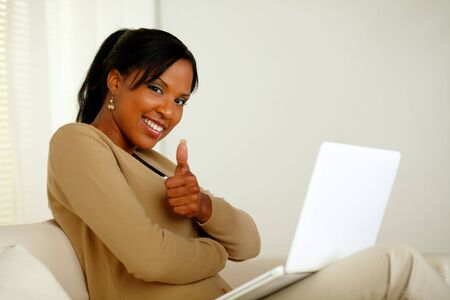 Portrait of a positive young afro-American woman in front her laptop while looking at you and lifting the finger up photo