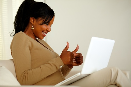 Portrait of a positive young woman looking to laptop screen while sitting on sofa at home indoor and lifting the fingers up Stock Photo - 14795013