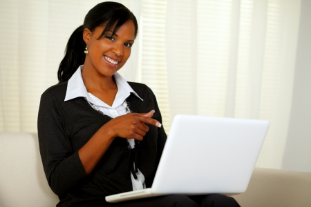 Portrait of a woman on black suit pointing to laptop screen while sitting on sofa at home indoor and looking at you photo