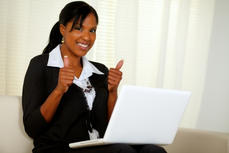 Portrait of young executive woman browsing the Internet on her laptop while lifting the fingers up photo