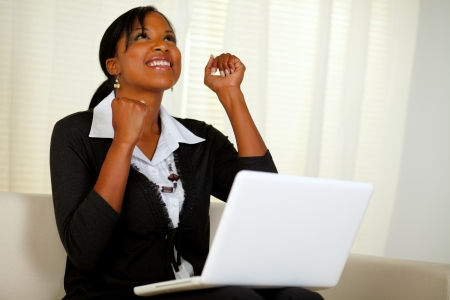 woman looking up: Portrait of a happy young entrepreneur woman celebrating a business victory on laptop and looking up while sitting on couch