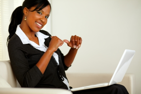 Portrait of a beautiful young business woman in front her laptop while pointing her fingers to her at home indoor photo