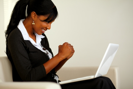 Portrait of an attractive woman on black suit celebrating a business victory while looking to her laptop and sitting on sofa at home