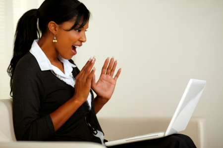 Portrait of a surprised executive young woman reading a great business news on laptop while sitting on couch photo