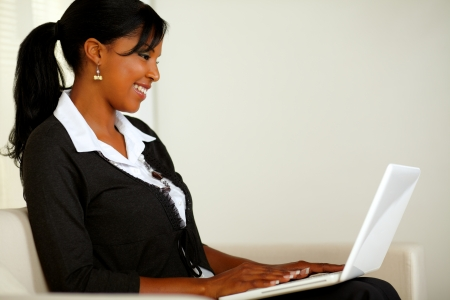 Portrait of a beautiful business black woman reading on laptop while sitting on couch photo