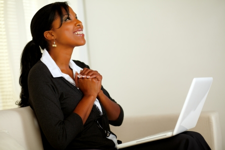 Portrait of a beautiful business woman on black suit smiling and looking up and thanking while sitting on sofa at home indoor photo