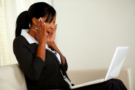 donna entusiasta: Ritratto di una donna dirigente eccitato giovane urlando con le mani in su mentre cerca di schermo del computer portatile e la lettura sorprendente grande novit� di un business aziendale