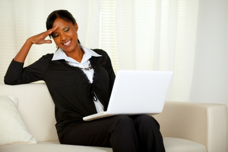 Portrait of a charming executive black woman reading on laptop screen. Sitting on a couch and laughing and having fun while working at home photo