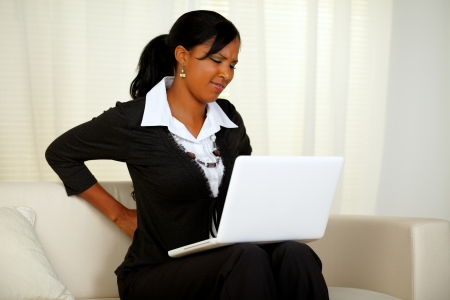 girls back to back: Portrait of a young businesswoman with back pain that is working on laptop at home indoor