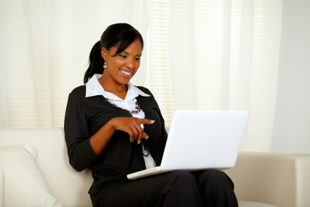 Portrait of an afro-American businesswoman on black suit pointing to laptop screen while sitting on sofa at home indoor photo