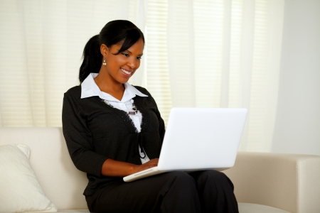 Portrait of an attractive woman on black suit working on laptop while sitting on couch at home indoor photo