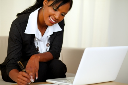 Portrait of a pretty businesswoman on black suit working while sitting on couch in front of her laptop photo