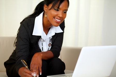 Portrait of a charming businesswoman on black suit working while sitting on couch in front of her laptop photo