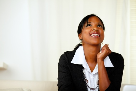 Portrait of an happy afro-American woman looking up on black suit at soft colors composition photo
