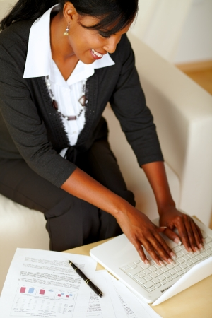 Top view portrait of an attractive businesswoman working on laptop on black suit while sitting on sofa photo