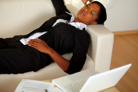 Top view portrait of a young executive woman lying on sofa with eyes closed and headache in front of her laptop photo
