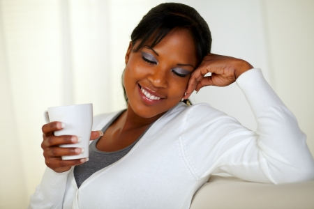 Portrait of an afro-American woman holding a white mug with close eyes while sitting pensive on couch at home indoor photo