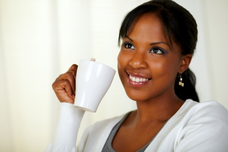Portrait of an attractive young woman drinking a cup of tea at soft colors composition