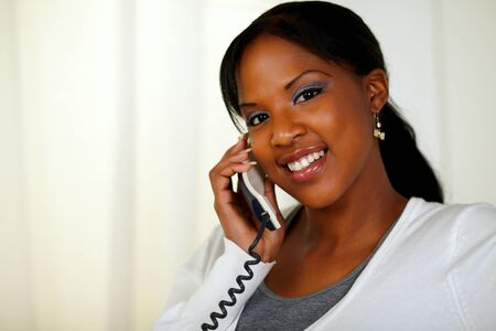 Portrait of a young female looking at you while talking on phone at soft colors composition Stock Photo