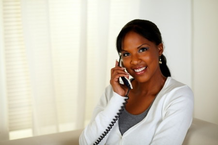 conversing: Portrait of a beautiful black woman conversing on phone at home indoor