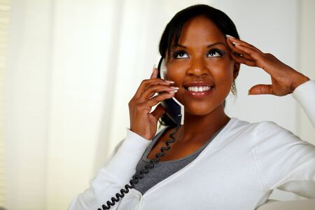 conversing: Portrait of a relaxed woman looking up and conversing on phone at soft composition Stock Photo