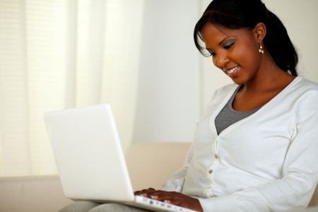 Portrait of an afro-American woman using her laptop at home indoor
