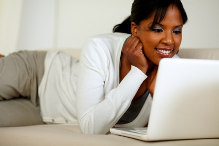 Portrait of an afro-American young woman reading on laptop screen while lying on sofa photo