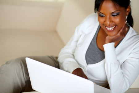 Portrait of a smiling afro-American woman using laptop while sitting on couch at home indoor Stock Photo - 14899570
