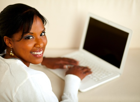 Portrait of a stylish female looking at you while working on laptop at home indoor. With copyspace Stock Photo - 14961925