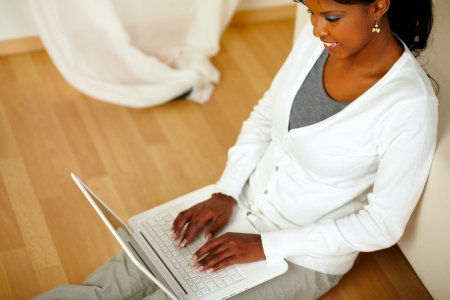 Top view portrait of a smiling afro-American female using a laptop at home indoor. With copyspace Stock Photo - 14961928