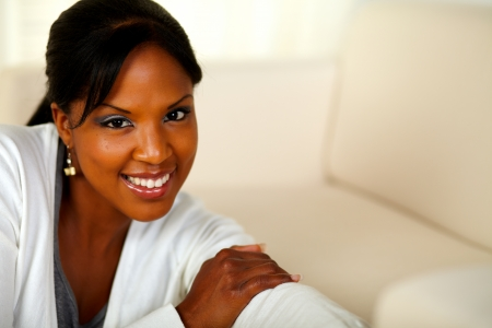Portrait of a stylish black female looking at you at home indoor. With copyspace photo