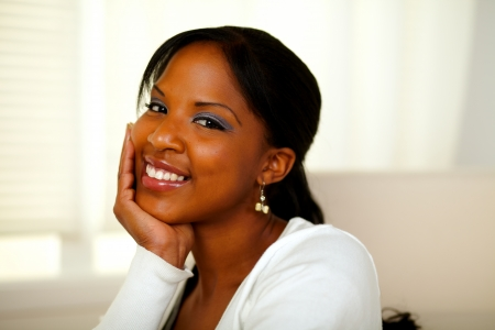 Portrait of a positive afro-american pretty woman looking and smiling at you. With copyspace photo