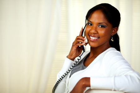 conversing: Portrait of a charming young woman smiling at you while conversing on phone. With copyspace