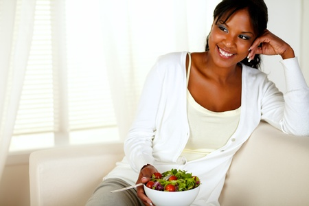 Portrait of a young female eating healthy salad lunch while sitting on couch at home indoor. With copyspace. photo
