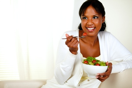 enyoing: Portrait of a lovely young woman enyoing fresh vegetable salad. With copyspace.