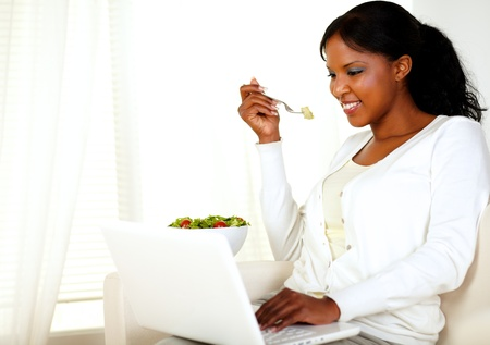 Portrait of a lovely young woman with a friendly smile, working on laptop and enjoying a green salad at home indoor photo
