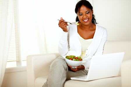 Portrait of an attractive young woman eating healthy salad while is sitting on couch in front of her laptop photo
