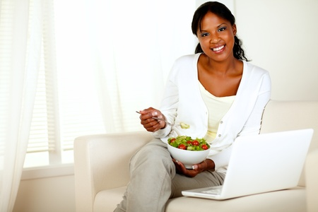 Portrait of a young woman eating healthy salad and looking at you while is sitting on couch in front of her laptop photo