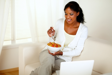 Portrait of a young female having breakfast and using her laptop at home indoor photo