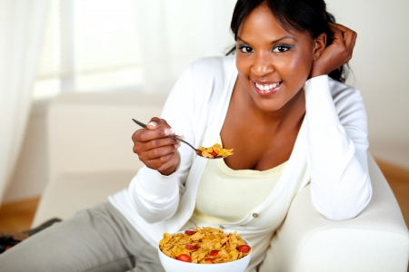 Portrait of a young woman smiling at you and having breakfast at home indoor. with copyspace photo