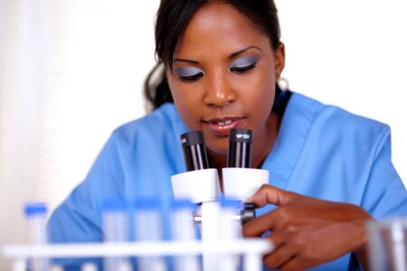 Young woman using a microscope at laboratory - portrait photo