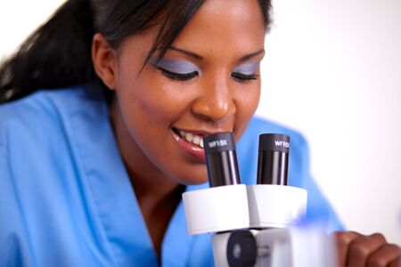 Medical doctor woman using a microscope at laboratory - portrait photo