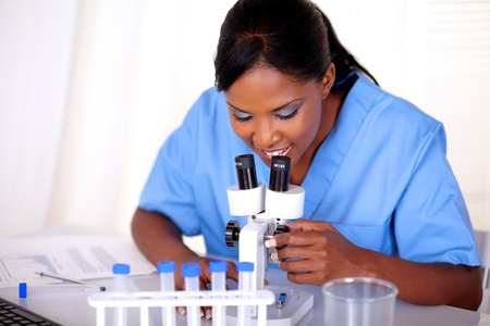 Medical doctor woman working with a microscope at hospital - portrait photo