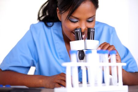 Charming scientific girl using a microscope at laboratory photo