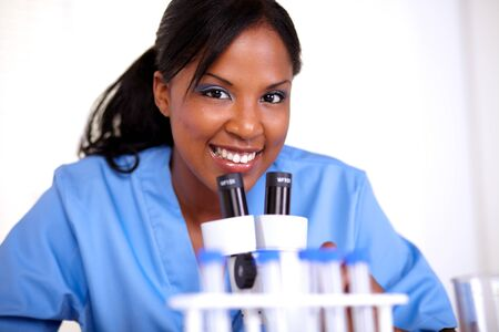 Scientific woman looking at you while working at laboratory with a microscope photo