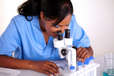 Scientific woman in blue uniform using microscope at laboratory photo