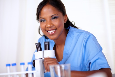 Scientific young woman looking at you while working at laboratory with a microscope photo