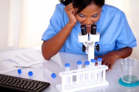 Afro-american scientific girl in blue uniform working at laboratory with a microscope and test tube photo