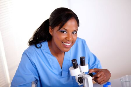Top view of a beautiful scientific woman looking at you while working at laboratory with a microscope photo